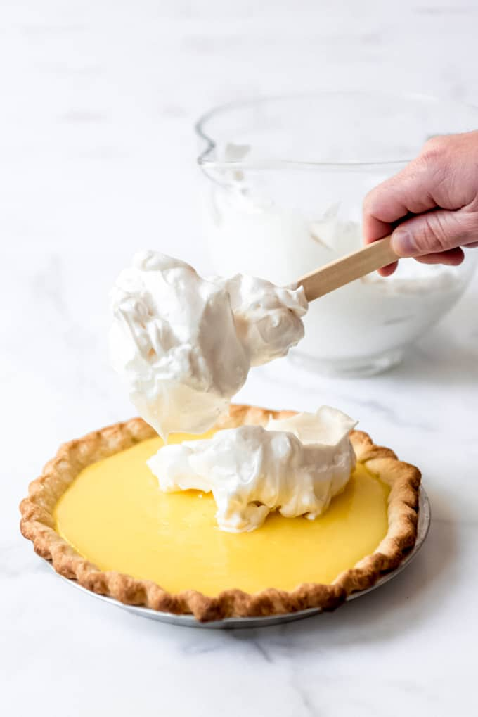 A hand dropping meringue onto lemon pie filling in a pie crust.