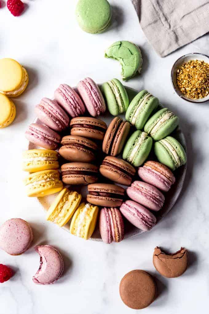 An image of pistachio, raspberry, chocolate, and lemon macarons on a plate.