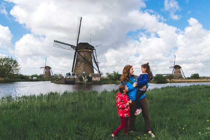 An image of a mother and two children in front of windmills at Kinderdijk in the Netherlands.