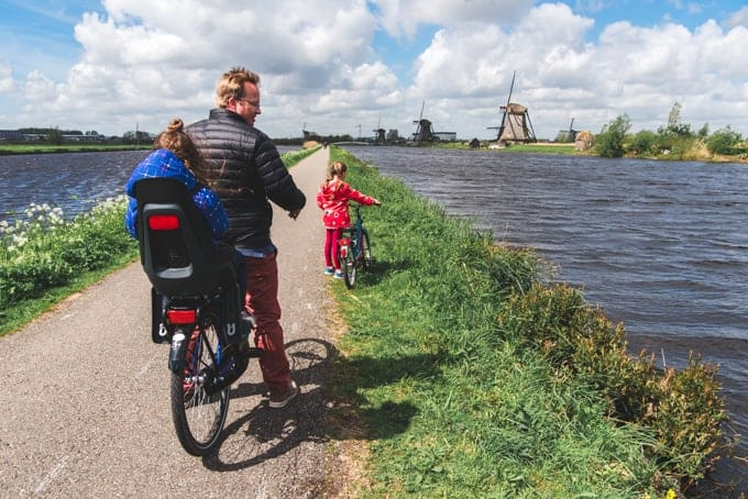 An image of a family riding bikes in the Netherlands at Kinderdijk.