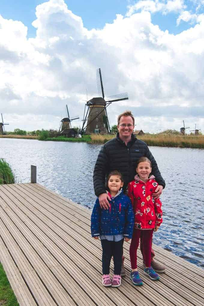 a man with his arms around his daughters posing for a photo on a dock in front of a river and windmills