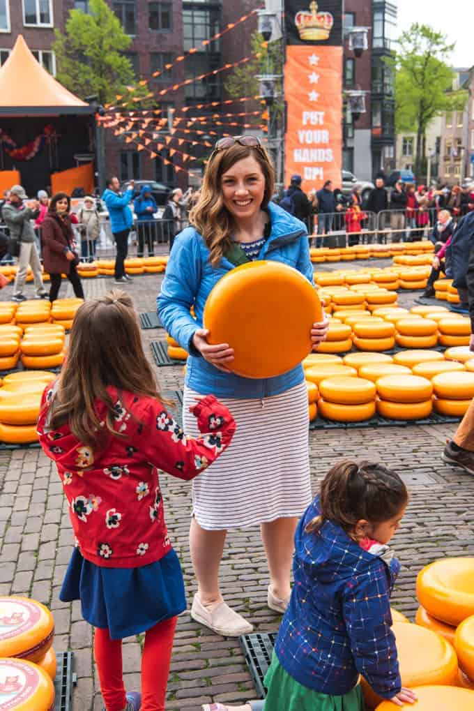 An image of a woman holding a large wheel of cheese at a cheese market in Alkmaar, Netherlands.