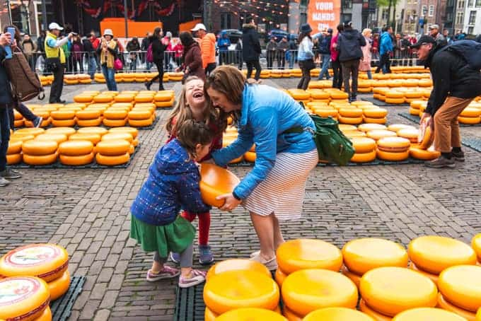 An image of a mom and her two young children lifting a wheel of cheese.