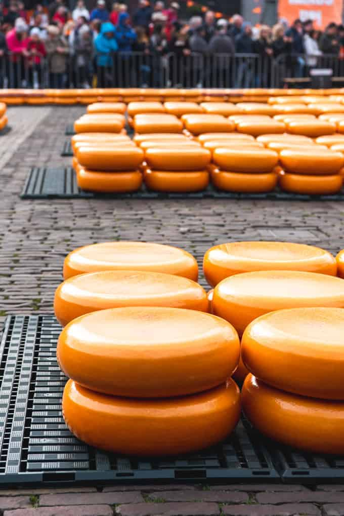 An image of cheeses stacked in an outdoor cheese market in Alkmaar, the Netherlands.