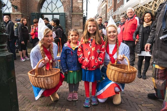An image of young children with Dutch girls in traditional costumes.