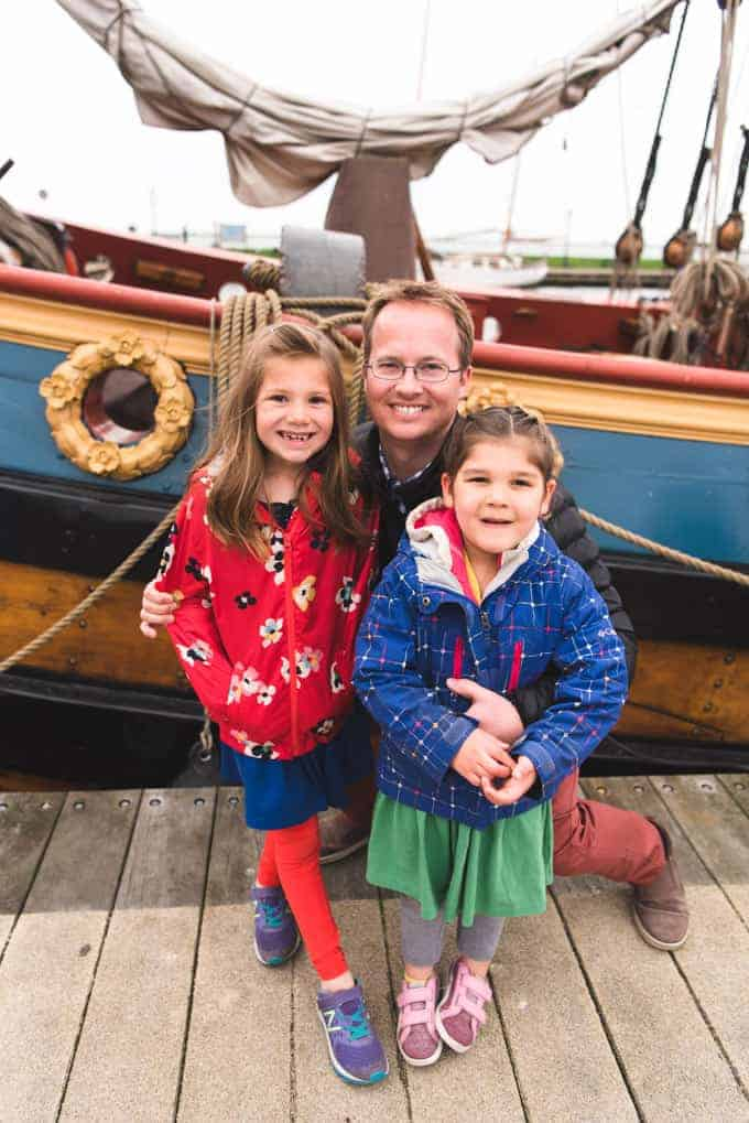 a man holding his 2 daughters and posing for a photo in front of a colorful boat