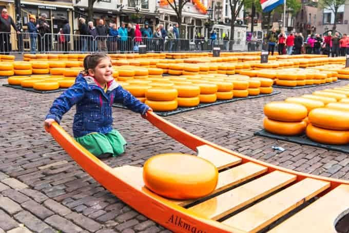 An image of a girl rocking a wooden sleigh with a large wheel of cheese no top