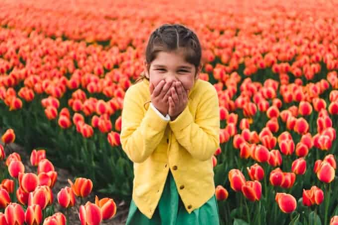 An image of a child giggling in a field of flowers.