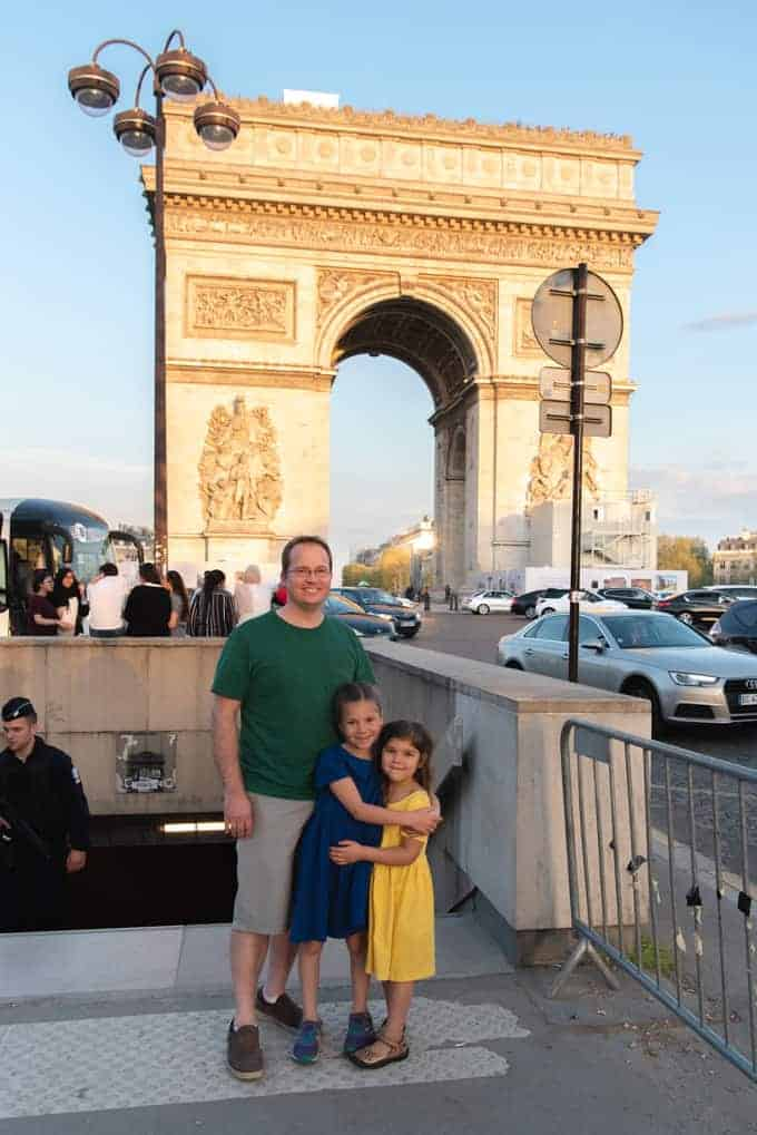 An image of a dad and kids in front of the Arc de Triomphe.