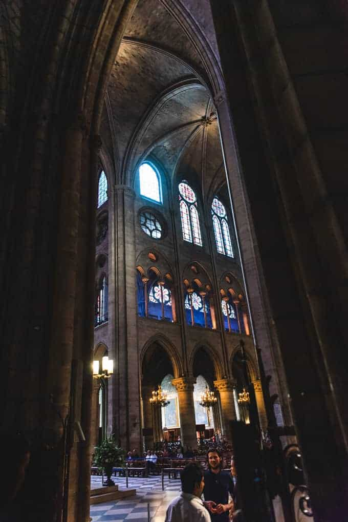An image of vaulted ceilings and stained glass windows in Notre Dame Cathedral.