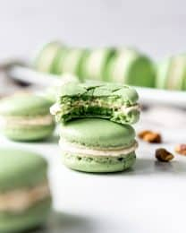 An image of a homemade pistachio macaron with a bite taken out of it.