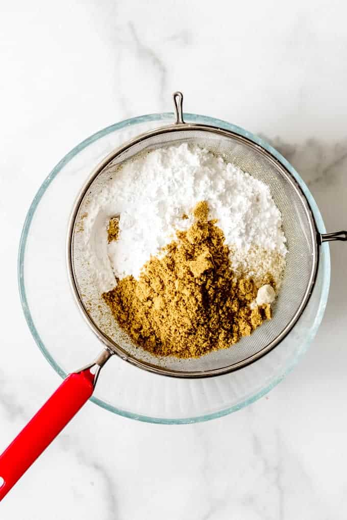 An image of almond flour, pistachio flour, and powdered sugar in a fine mesh sieve.