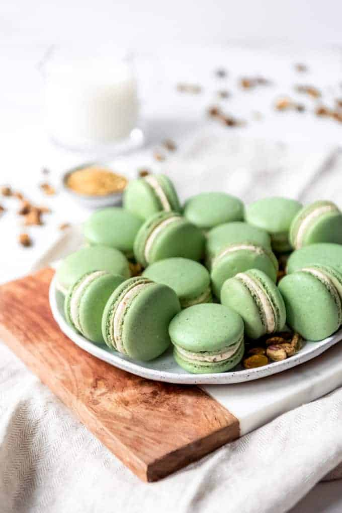 An image of a plate of French macarons with pistachio buttercream filling.