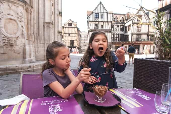 An image of kids enjoying chocolate mousse in France.