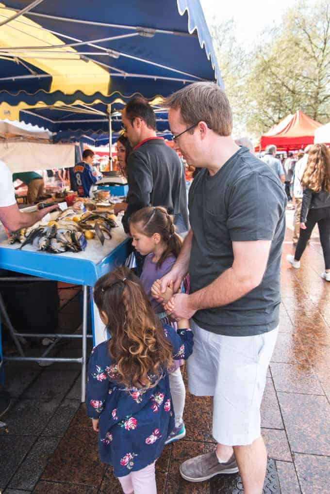 An image of a father and kids visiting a market in Rouen, France.