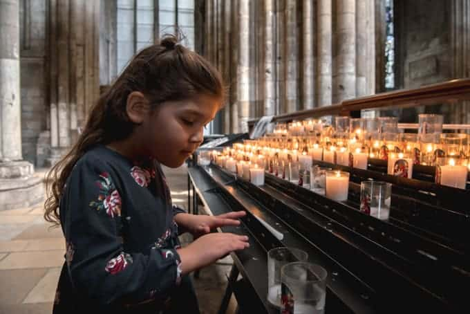 An image of a child looking at lighted candles in a cathedral in Rouen, France.