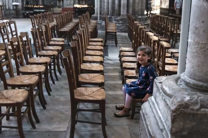 An image of a child sitting on a kneeling bench in a cathedral in France.