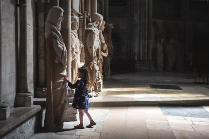 An image of a child looking at statues in a cathedral in France.