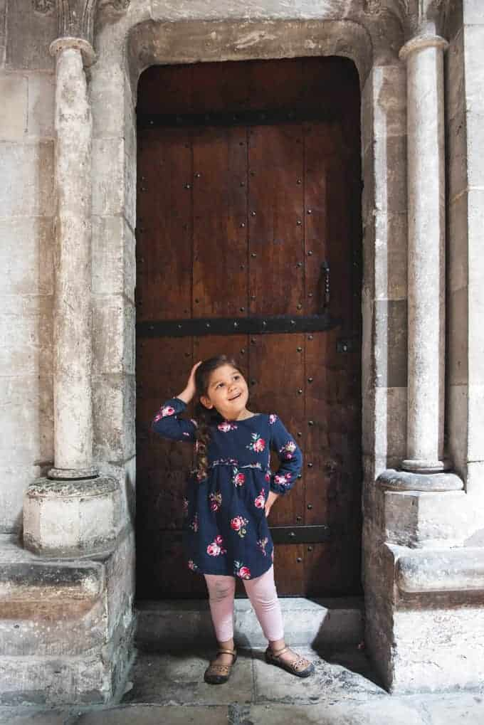 An image of a young girl posing in front of a medieval door.