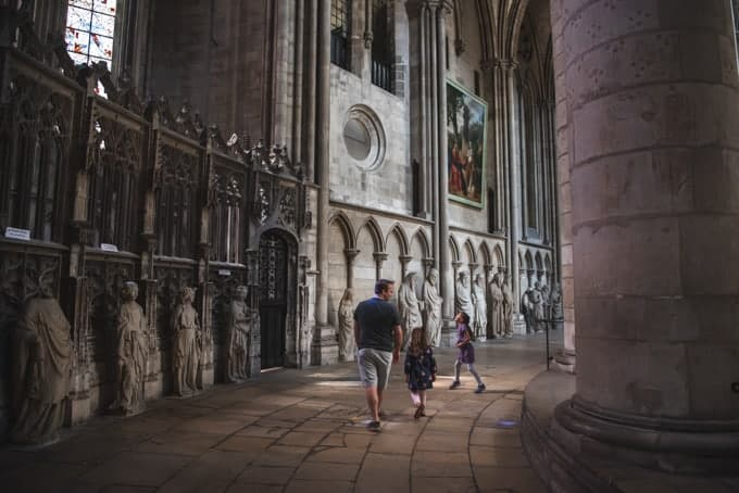 An image of a father and children walking through a cathedral in Rouen, France.
