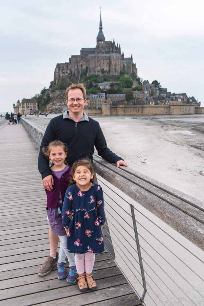 An image of a dad and two young daughters in front of Mont Saint-Michel in France.