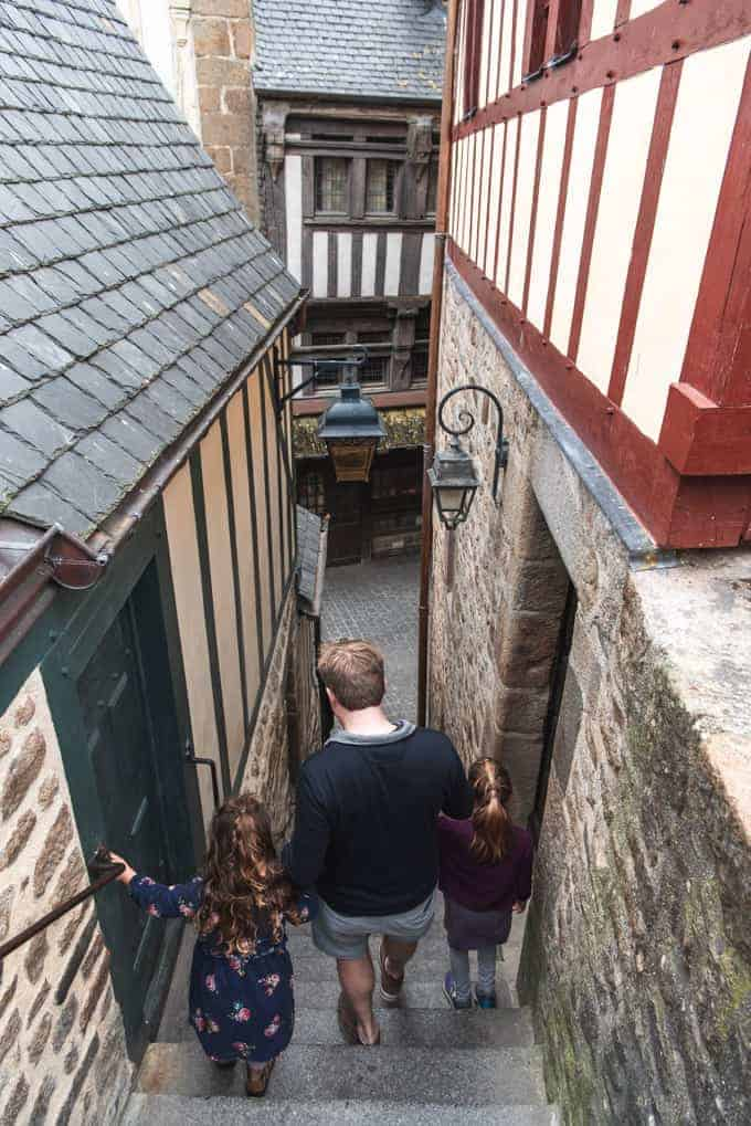 An image of a father and children going down a narrow staircase in Mont St. Michel.