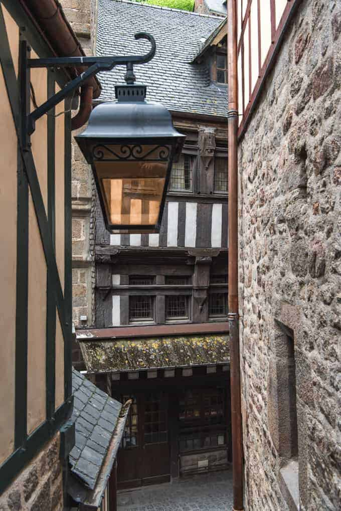 An image of a lamp hanging off the side of a house in Mont Saint-Michel.