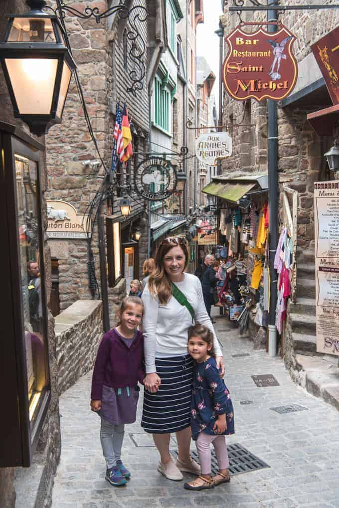 An image of a mother and children on a cobblestone street in Mont Saint-Michel.