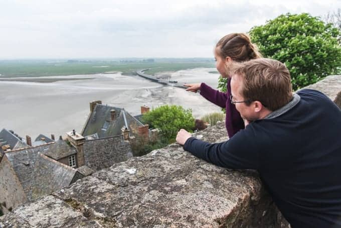 An image of a father and daughter looking out at the view from the top of Mont Saint-Michel.