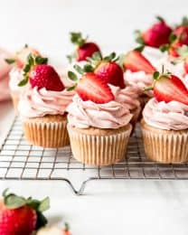 Every bite of these moist Fresh Strawberry Cupcakes is a taste of sweet summer-ripe strawberries in from-scratch homemade cupcake with a light strawberry buttercream frosting swirled on top. It handily beats the pants off a strawberry cake mix any day, without any artificial strawberry flavor! #cupcakes #strawberry #homemade #fresh #fromscratch #frosting #best #easy #moist #recipe