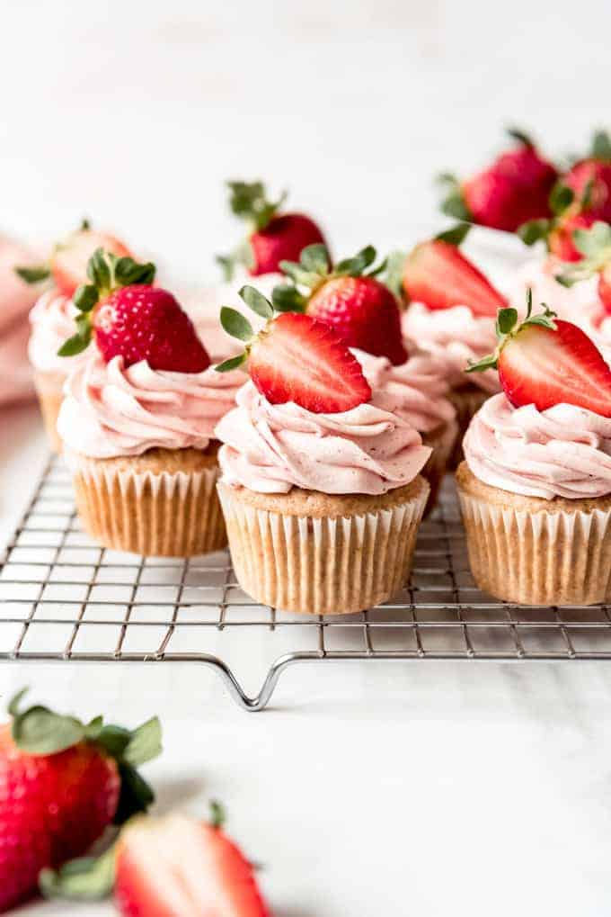 An image of fresh strawberry cupcakes with strawberries on top.