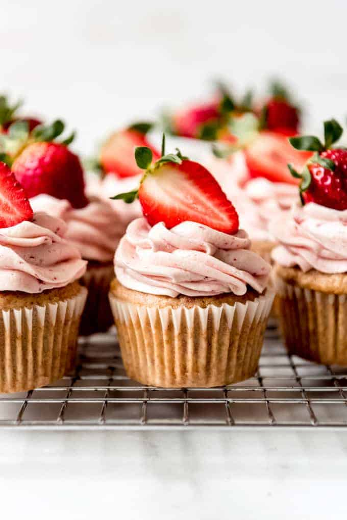 An image of strawberry cupcakes on a wire rack.