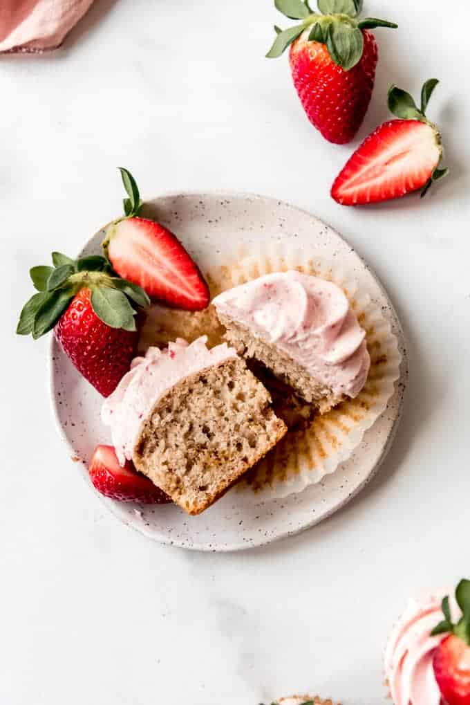 An image of a pink strawberry cupcake sliced open on a plate.
