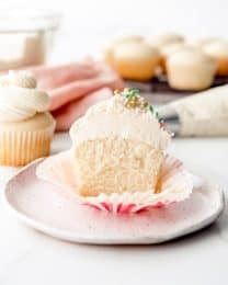 An image of a vanilla cupcake with vanilla buttercream that is cut in half.