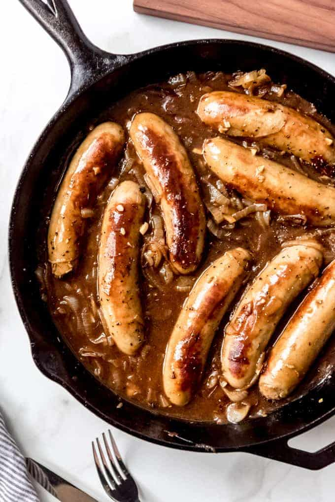 An image of cooked sausages in a pan with onion gravy.