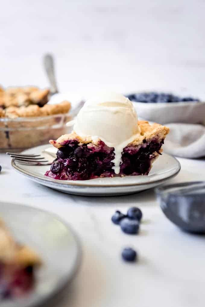 A slice of blueberry pie from scratch with vanilla ice cream melting on it.