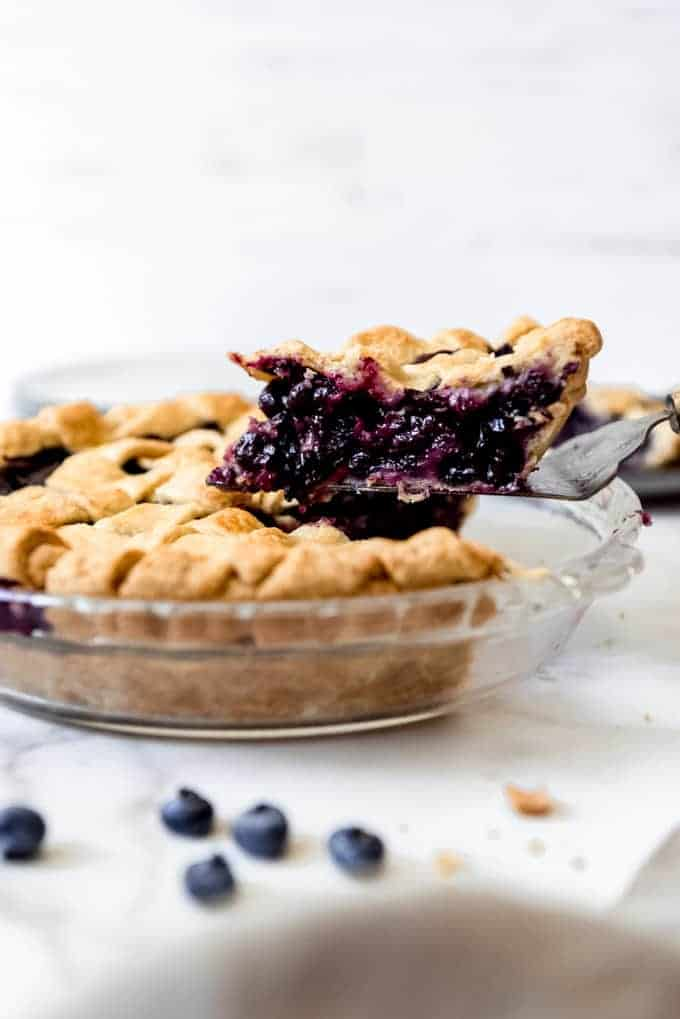 A slice of the best blueberry pie being lifted out of the pie pan.