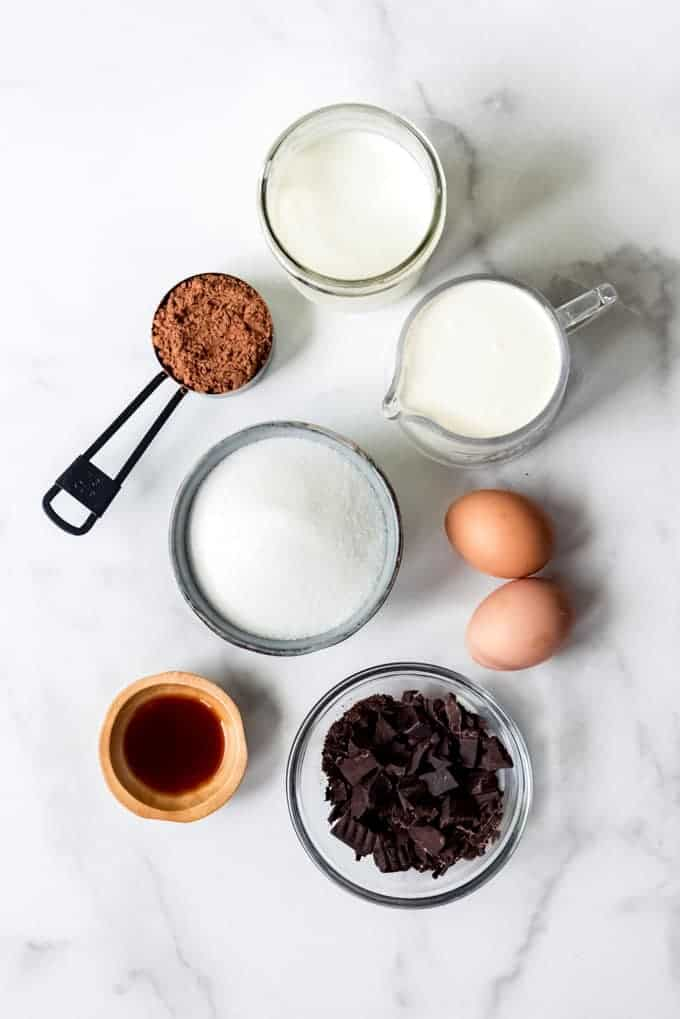 The ingredients for chocolate ice cream separated into individual bowls or containers on a marble surface.