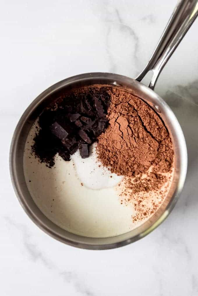 A saucepan with cream, milk, sugar, cocoa powder, and chopped unsweetened chocolate on a marble surface.