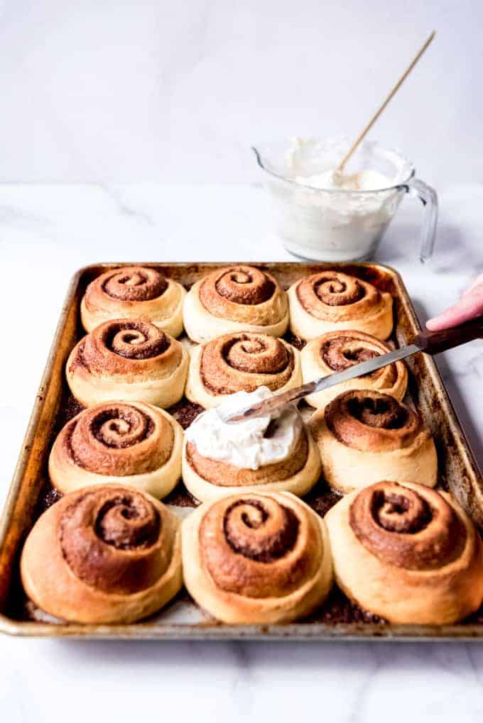 An image of a pan of freshly baked cinnamon rolls being topped with cream cheese frosting.