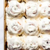 An image of a pan of frosted homemade cinnamon rolls with cream cheese icing.