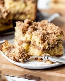 An image of a piece of sour cream coffee cake with a bite taken out of it.