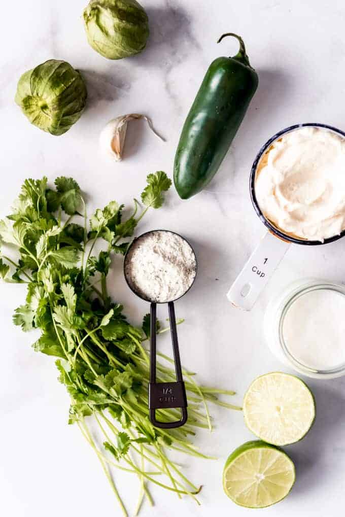 The ingredients for making creamy cilantro lime dressing arranged on a marble surface.