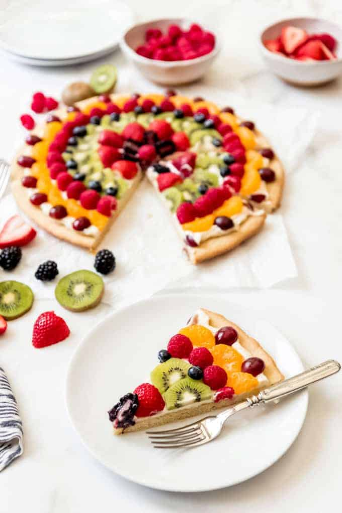 An image of a slice of fruit pizza on a white plate.
