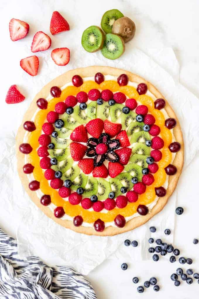 An image of a fruit pizza decorated with fresh kiwi, raspberries, strawberries, grapes, blueberries, and mandarin oranges.