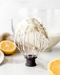 An image of a kitchenaid whisk attachment covered in homemade lemon buttercream frosting.