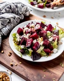An image of roasted beet salad with goat cheese and pistachios on a plate.