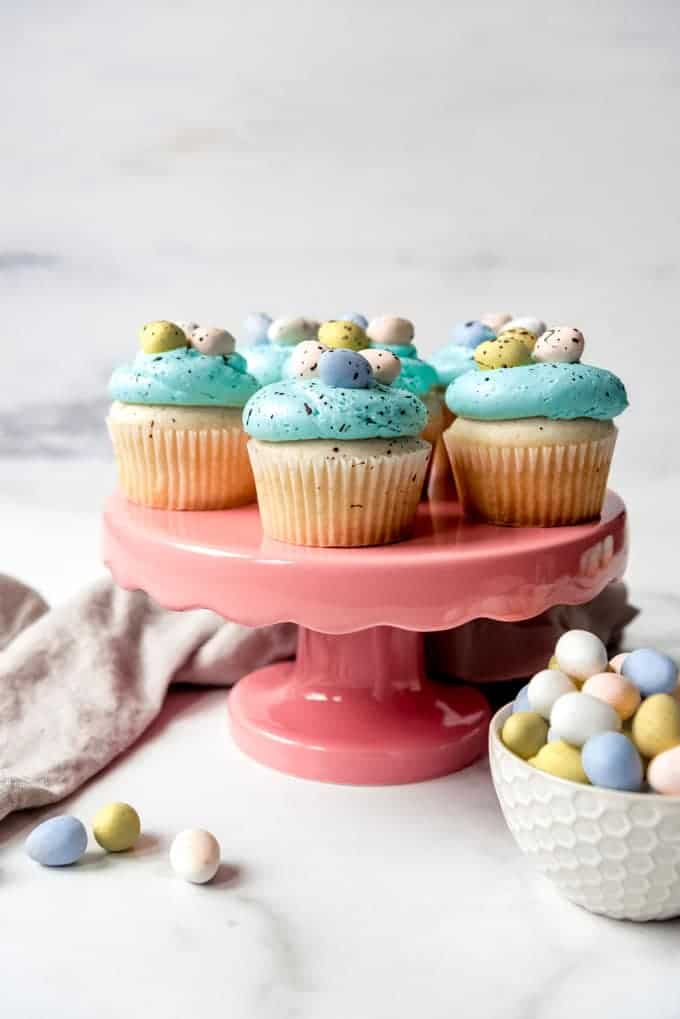 An image of vanilla Spring cupcakes with blue frosting decorated to resemble robin's eggs on a pink cake stand.