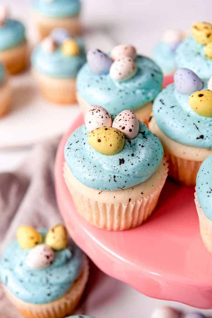 An image of white cupcakes with blue frosting, decorated with easter candy.