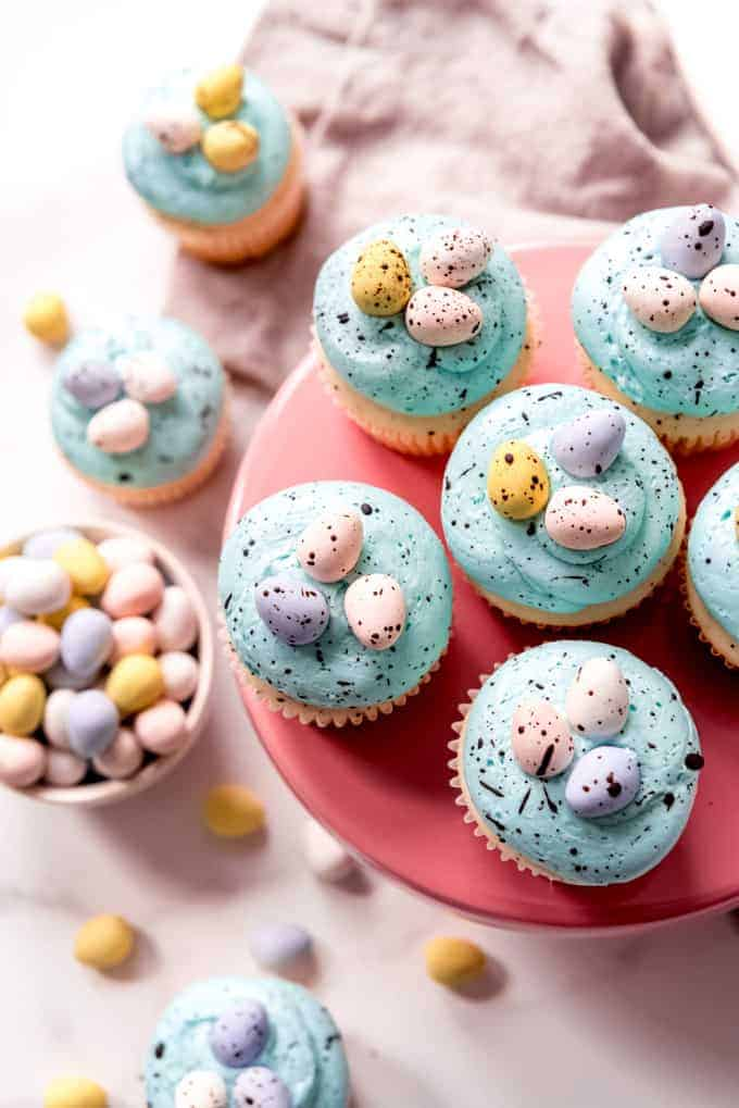 An image of homemade blue frosted easter cupcakes on a pink cake stand.